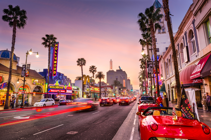 Los Angeles, USA - March 1, 2016: Traffic and pedestrians on Hollywood Boulevard at dusk. The theater district serves as a famous tourist attraction.