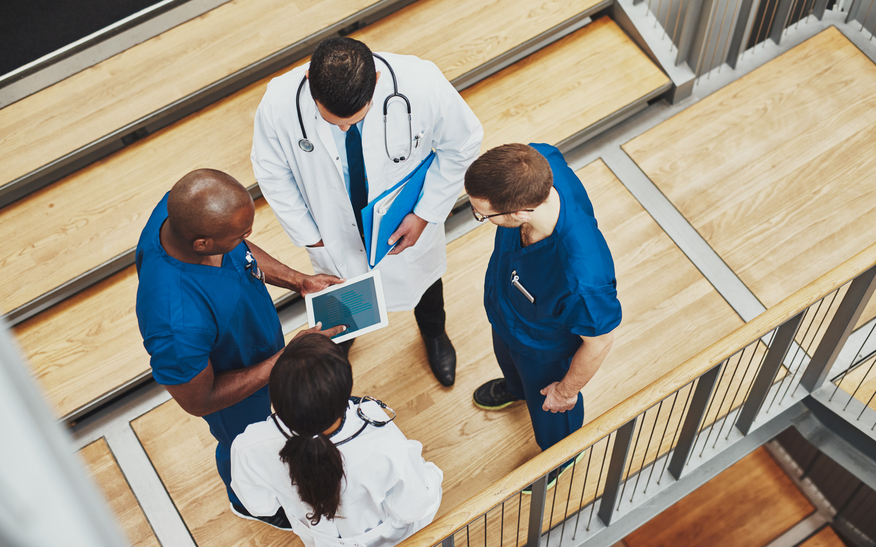 Multiracial medical team having a discussion as they stand grouped together around a tablet computer on a stair well, overhead view